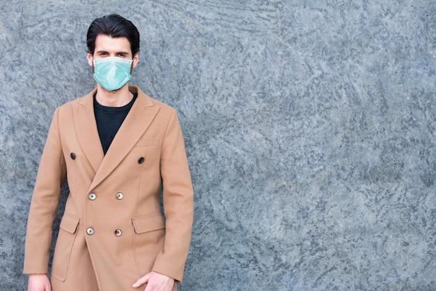 Uomo davanti al muro mentre indossa una maschera, concetto di pandemia di coronavirus