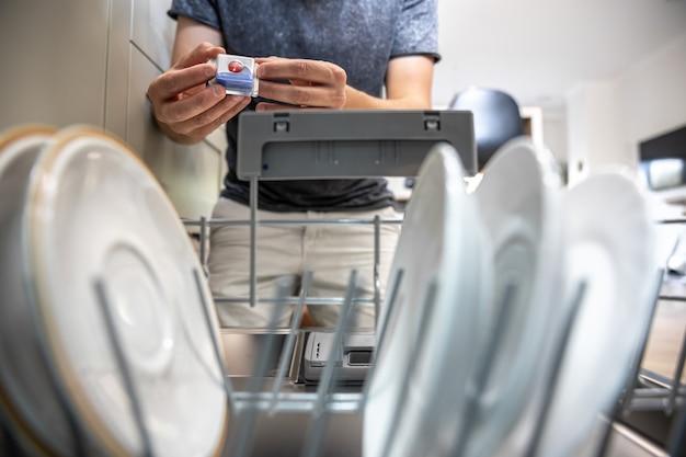 Un uomo di fronte a una lavastoviglie aperta tiene una compressa di detersivo per piatti nella lavastoviglie.