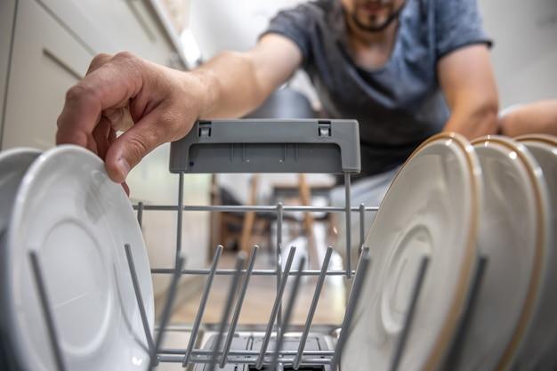 Un uomo davanti a una lavastoviglie aperta tira fuori i piatti puliti dopo averli lavati.
