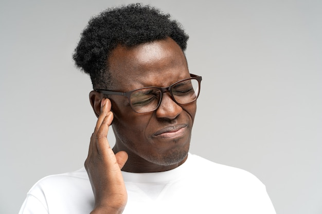 Uomo accigliato che soffre di tinnito palpitante mal d'orecchi stanco del rumore che tocca l'orecchio doloroso