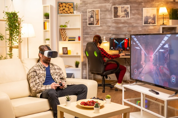 Uomo giocatore che utilizza un auricolare vr per giocare ai videogiochi in salotto a tarda notte
