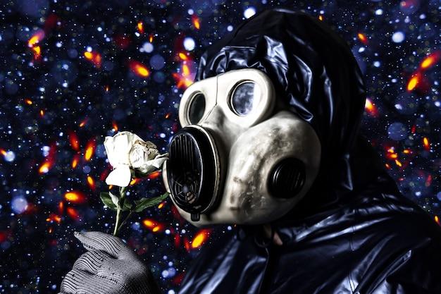 Uomo nella maschera antigas che tiene il fiore. influenza delle radiazioni. inquinamento ambientale. concetto di chernobyl. energia nucleare pericolosa. disastro ecologico.