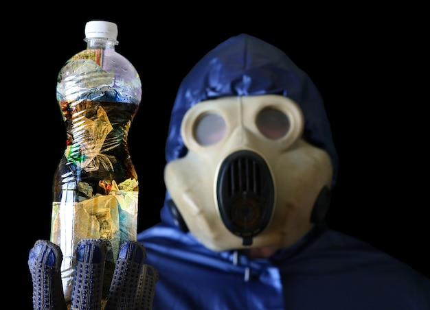 Uomo nella maschera antigas che tiene una bottiglia di plastica con acqua sporca. inquinamento ambientale. disastro ecologico.