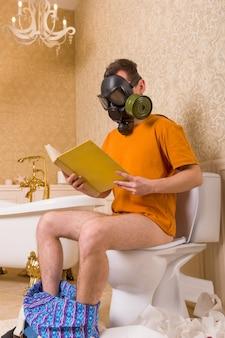 Uomo in maschera antigas seduto sul water e leggere il libro