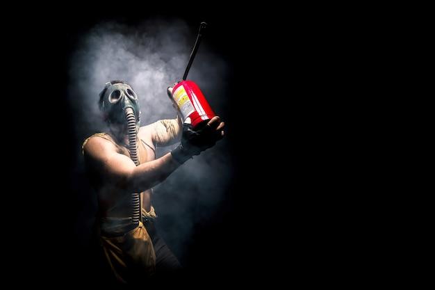 Uomo con la maschera antigas con estintore, sopravvivenza umana dopo l'apocalisse.