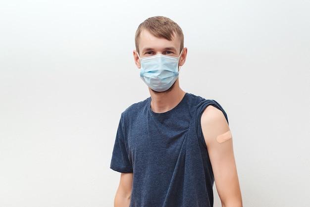Uomo che si fa vaccinare contro il covid. persona che indossa la maschera facciale. uomo felice che mostra il braccio con la fasciatura dopo aver ricevuto il vaccino. vaccinazione, immunizzazione, inoculazione e pandemia di coronavirus.