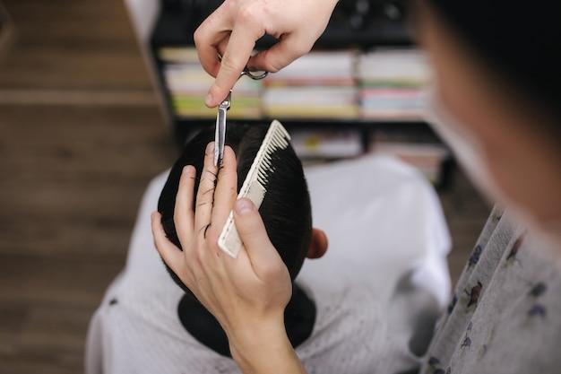 Uomo che si taglia i capelli dal barbiere indossando una maschera durante la pandemia di coronavirus. barbiere professionista che indossa guanti. covid-19, concetto di bellezza, cura di sé, stile, sanità e medicina.