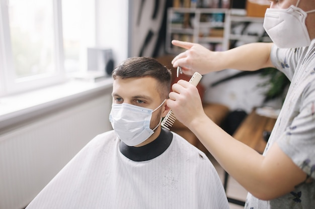 Uomo che ottiene i capelli tagliati a forbice nel negozio di barbiere. il barbiere usa le forbici e indossa una maschera durante la pandemia di coronavirus. barbiere professionista lavora a casa. quarantena per il covid19.