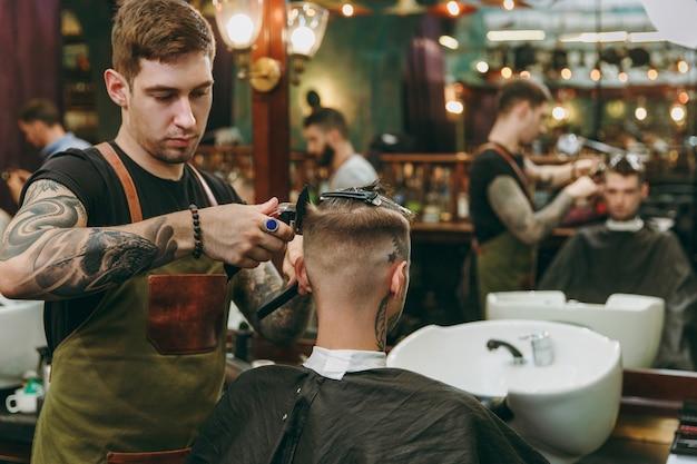 Uomo che ottiene taglio di capelli alla moda al negozio di barbiere. l'hairstylist maschile in tatuaggi al servizio del cliente.