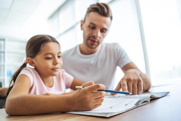 L'uomo e una ragazza che fanno i compiti alla scrivania