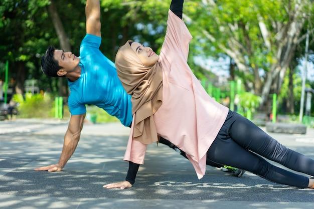 Un uomo e una ragazza con un velo in abiti da palestra che fanno esercizi per le mani insieme nel parco