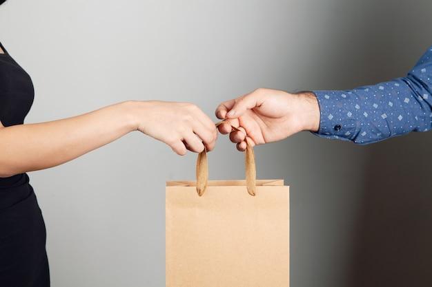 L'uomo dà la borsa regalo alla donna su sfondo grigio