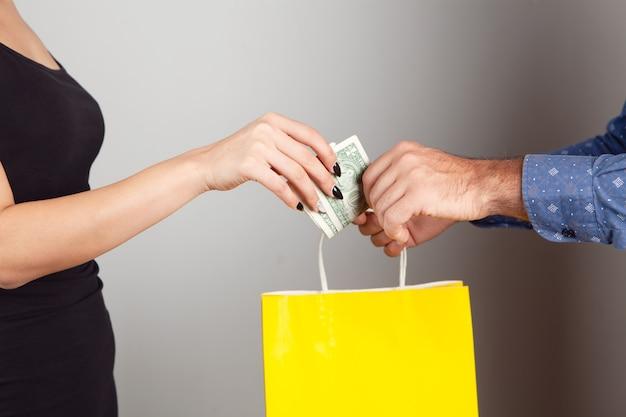 Un uomo regala un pacco regalo e una donna lo paga. concetto di acquisto