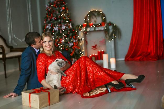 Un uomo fa un regalo alla sua amata donna alla vigilia di capodanno. l'uomo è vestito con un abito elegante e la donna con un lungo abito da sera rosso.