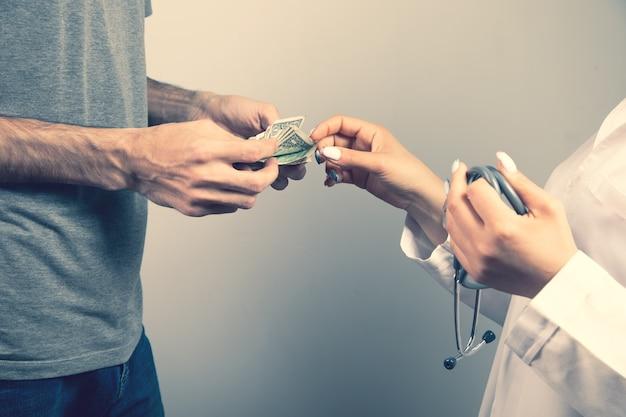 Un uomo dà soldi a un medico su uno sfondo grigio