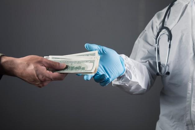 Un uomo dà soldi a un dottore su una scena grigia
