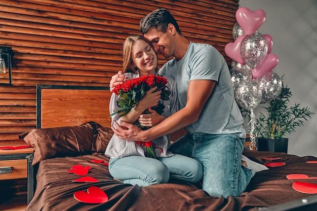Un uomo regala a una donna un mazzo di rose rosse. una coppia è seduta sul letto con coriandoli a forma di cuore.