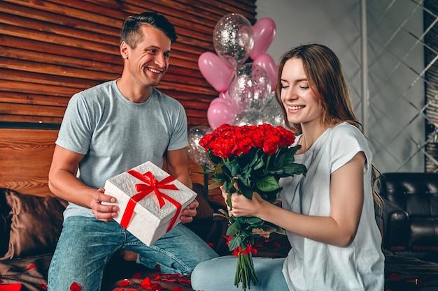 Un uomo dà a una donna un regalo e rose rosse. una coppia è seduta sul letto con coriandoli a forma di cuore.