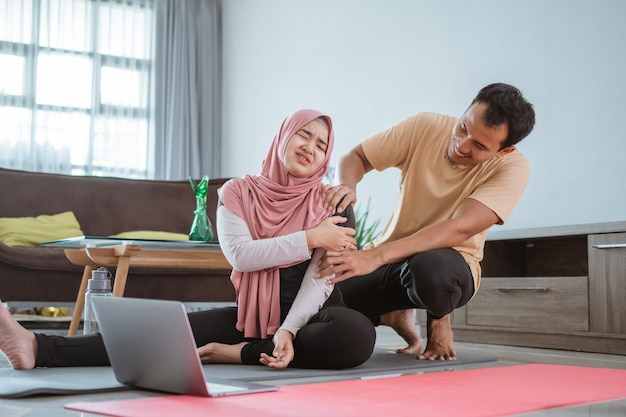 Uomo che dà massaggio a sua moglie durante l'allenamento a casa insieme. lesioni durante l'allenamento a casa