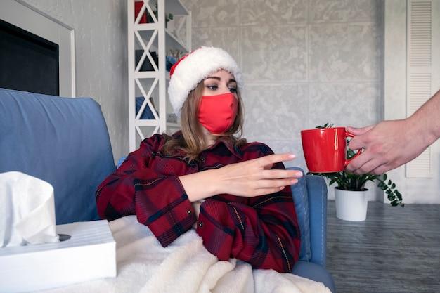 Uomo che dà tazza rossa con tè caldo alla giovane donna ammalata sdraiata sul divano in coperta bianca che indossa maschera protettiva medica e cappello di natale a casa