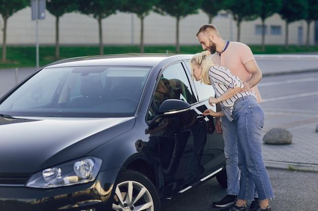 Uomo che dà sorpresa alla donna acquistando una nuova auto. giovani coppie felici vicino alla nuova automobile all'aperto. acquisto di un'auto.