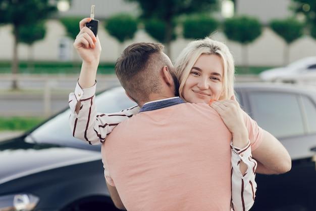 Uomo che dà sorpresa alla donna acquistando una nuova auto. la giovane coppia compra un'auto, l'uomo e la donna stanno abbracciando vicino all'auto sulla strada. donna che mantiene le chiavi della macchina nelle sue mani.