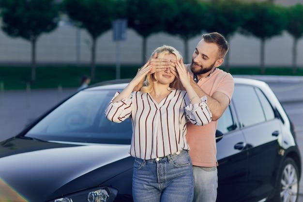 Uomo che dà sorpresa alla donna acquistando una nuova auto. la giovane coppia acquista un'auto, un uomo e una donna sono in piedi vicino all'auto sulla strada. regalo a sorpresa per una persona cara.