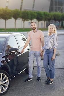 Uomo che dà sorpresa alla donna acquistando una nuova auto. giovane coppia, uomo e donna, acquista un'auto all'aperto. acquisto di una nuova auto dal salone. fai una prova su strada con una macchina nuova.