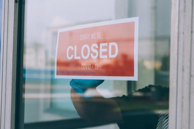 Uomo dietro una porta a vetri con un segno