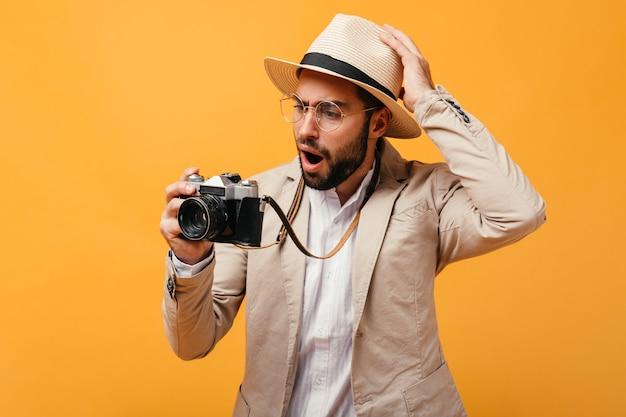 Uomo in occhiali e cappello beige in posa con fotocamera retrò retro