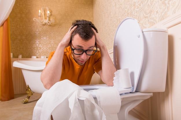 L'uomo con gli occhiali si siede appoggiando le mani sul water. interno del bagno in stile vintage