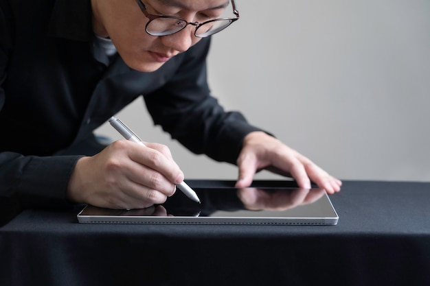 Uomo in vetri facendo uso della penna digitale che attinge progettazione digitale della compressa, dell'architettura o dell'ingegnere progettazione sullo schermo della compressa, concetto astuto di tecnologia dello schermo digitale