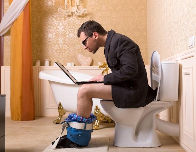 Uomo in bicchieri con il computer portatile seduto sulla tazza del water. interno del bagno di lusso in stile vintage