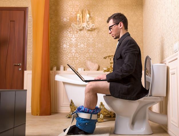 Uomo in bicchieri con il computer portatile che si siede sulla tazza del water