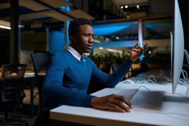 L'uomo con gli occhiali lavora al computer, stile di vita in ufficio