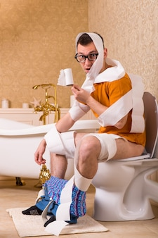 Uomo in bicchieri avvolti in carta igienica seduto sulla ciotola. interno del bagno in stile vintage