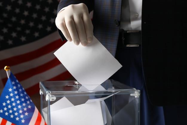 Uomo in guanto mettendo scheda elettorale nella casella di voto contro la bandiera americana