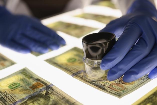 Uomo in guanti che controllano denaro contraffatto con il primo piano della lente d'ingrandimento. concetto di denaro falso