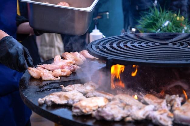 Un uomo in guanti gira delicatamente gli spiedini con carne di pollo marinata alla griglia o pinze da barbecue. il processo di cottura della carne sui carboni con fumo. barbecue nel cortile