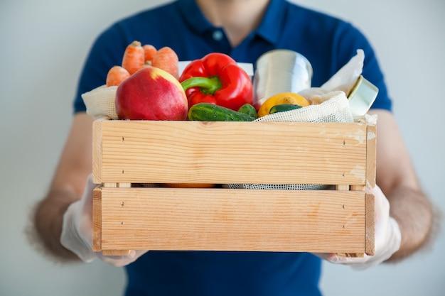 Uomo in guanti che tengono una scatola piena di cibo