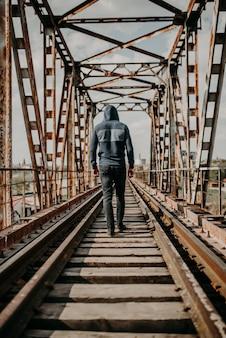 Un uomo va per ferrovia in lontananza