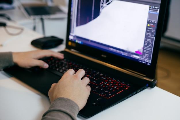 Grafico uomo che lavora al laptop su un progetto, in ufficio