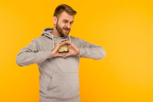 Uomo in una felpa con cappuccio grigia tiene una carta di credito nelle sue mani