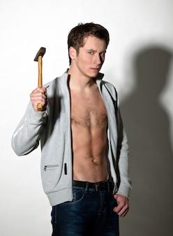 Uomo in giacca grigia e jeans in posa mentre levandosi in piedi con il martello in mano