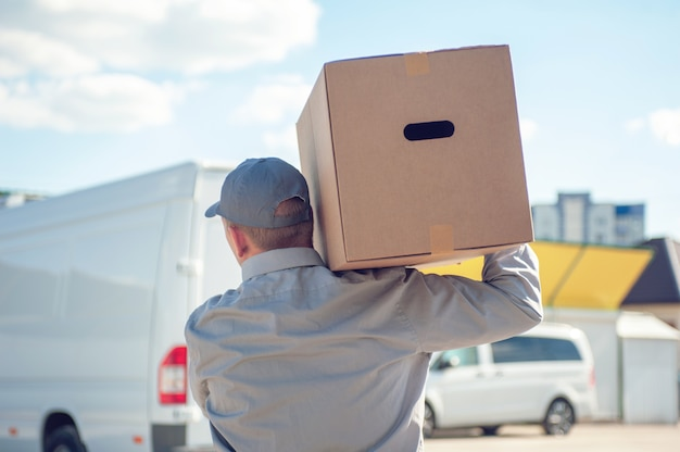 Un uomo vestito di grigio tra le mani con una scatola di cartone contro lo spazio del furgone