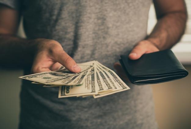 Un uomo con una maglietta grigia tiene in mano dollari e portafoglio nero. banca. casinò. stipendio. aliquote.