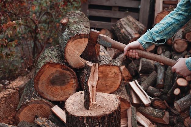 L'uomo in camicia a scacchi verde si prepara a tagliare. tenuta dell'ascia arrugginita