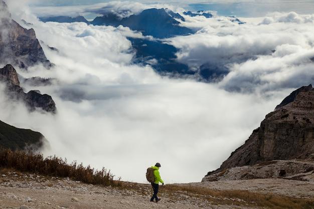 Uomo in una giacca verde con uno zaino escursionismo sulle alpi dolomitiche coperto di nuvole, splendida vista nel parco delle tre cime di lavaredo, italia