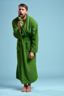 Un uomo in una veste verde in piena crescita su sfondo blu a piedi nudi