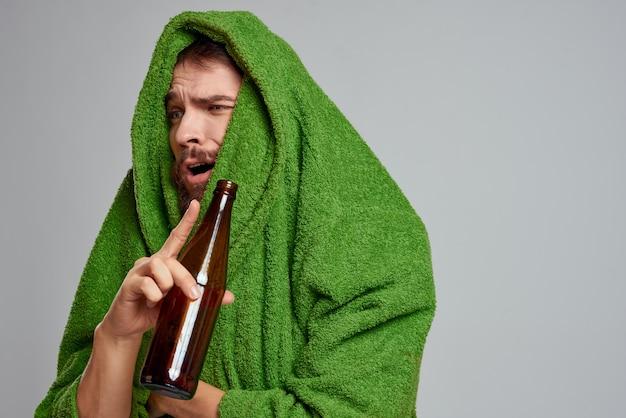 Un uomo vestito di verde con una bottiglia di alcol è dispiaciuto